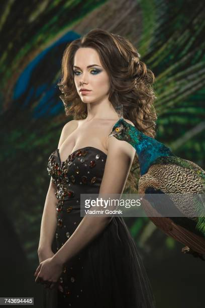 Woman wearing strapless dress while standing by peacock against feathers