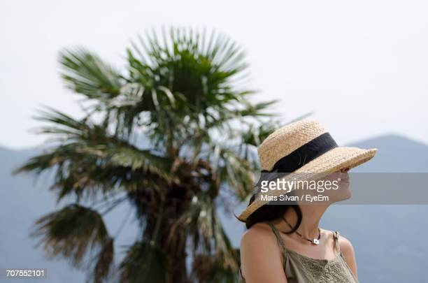Woman Wearing Straw Hat With Palm Tree In Background