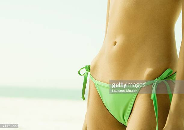 Woman wearing string bikini, close-up of abdomen