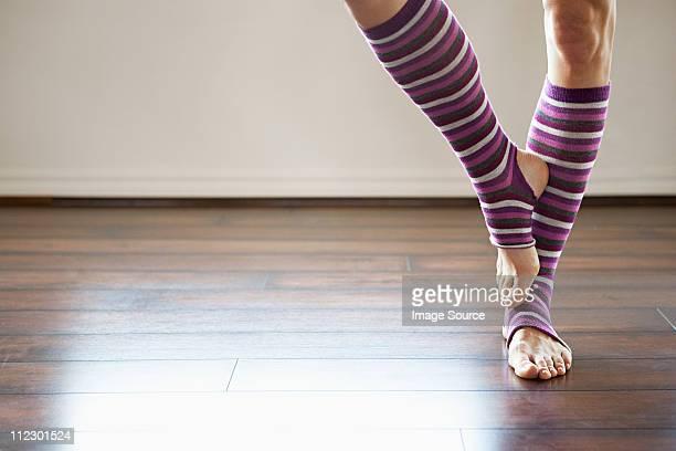 woman wearing stripey legwarmers standing on one leg - レッグウォーマー ストックフォトと画像