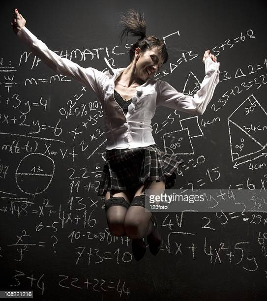woman wearing suggestive school uniform jumping in front of blackboard - garter belt stock pictures, royalty-free photos & images
