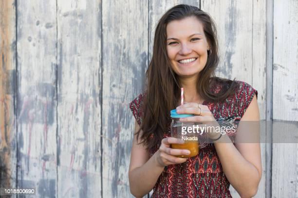 Frau Sommerkleid trägt und hält ein kaltes Getränk