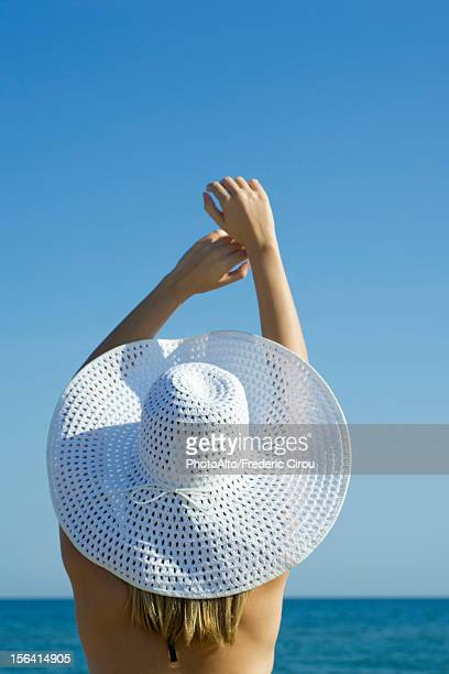 Woman wearing sun hat at the beach, rear view