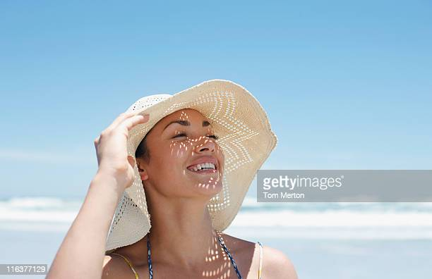 woman wearing sun hat on beach - sun hat stock pictures, royalty-free photos & images