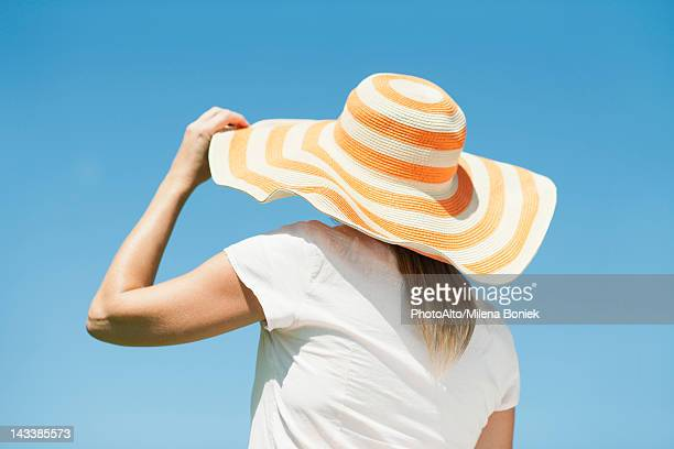 woman wearing sun hat, rear view - sun hat stock pictures, royalty-free photos & images