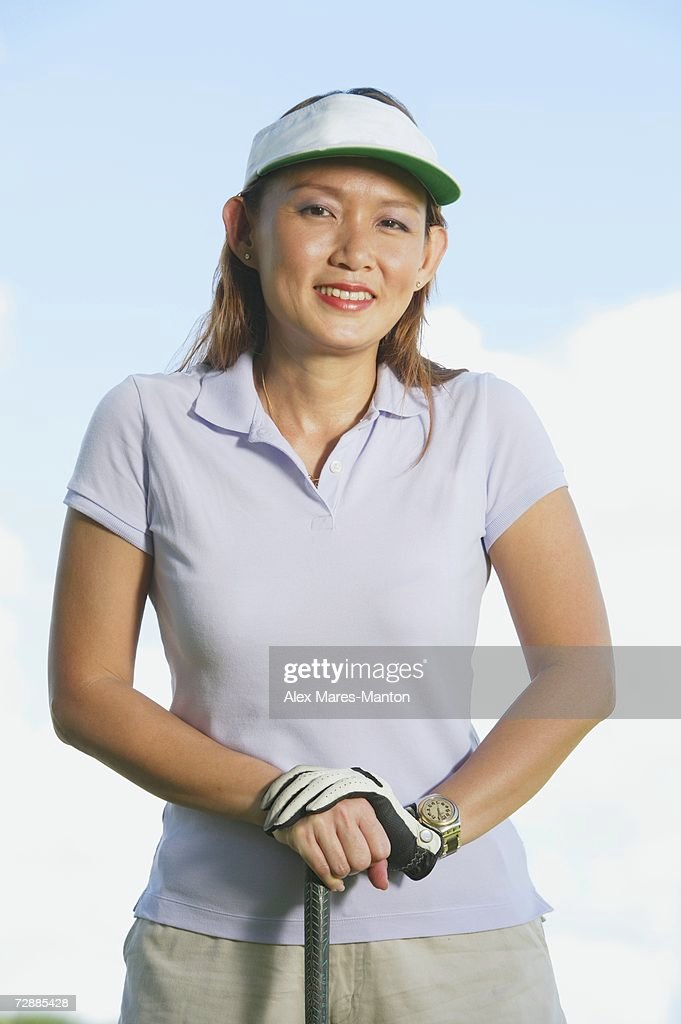 7517bd20 Woman Wearing Sun Visor Leaning On Golf Club Stock Photo - Getty Images
