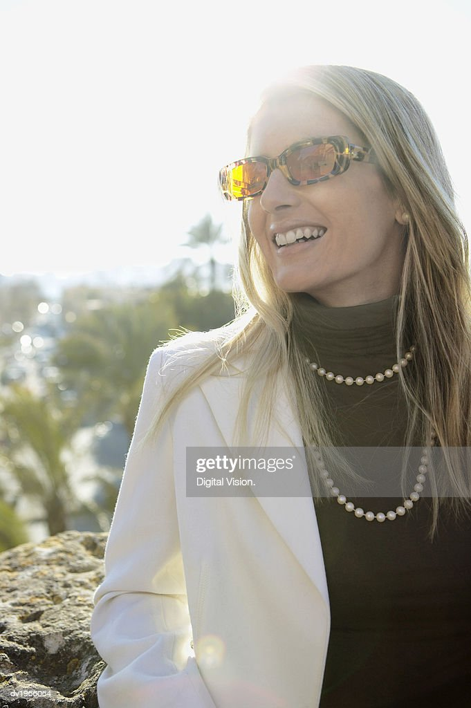 Woman Wearing Sunglasses and a Pearl Necklace Looking Sideways : Stock Photo