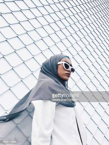 woman wearing sunglasses and hijab while standing against wall - hijab stock pictures, royalty-free photos & images