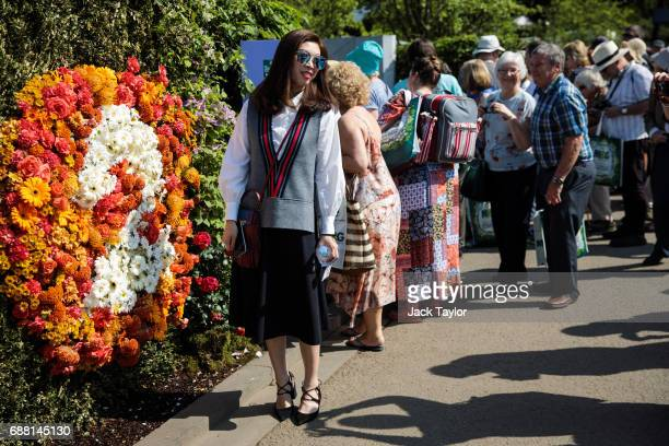 A woman wearing sunglasses poses for a photograph by a floral display at the Chelsea Flower Show on May 25 2017 in London England Visitors enjoy warm...
