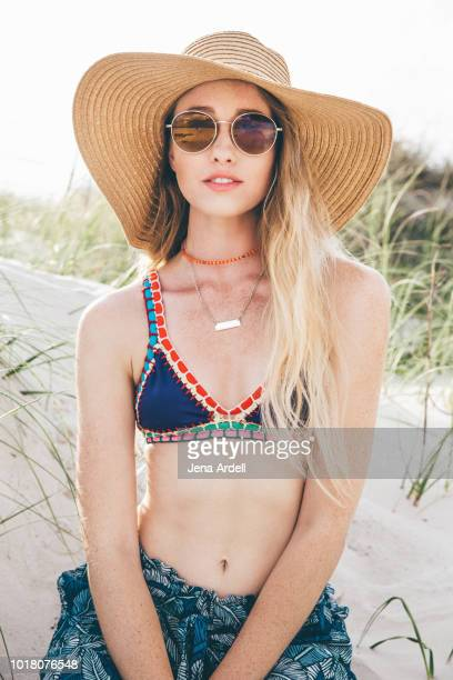 woman wearing sunglasses, round sunglasses, woman wearing beach hat, woman wearing sun hat, sun protection, woman fair complexion, woman fair skin - straw hat stock pictures, royalty-free photos & images