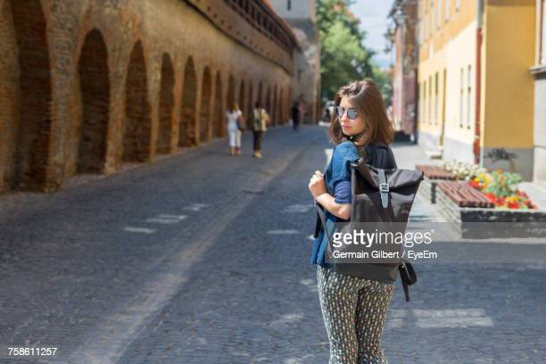 Woman Wearing Sunglasses Standing On Street Against Old Ruins In City