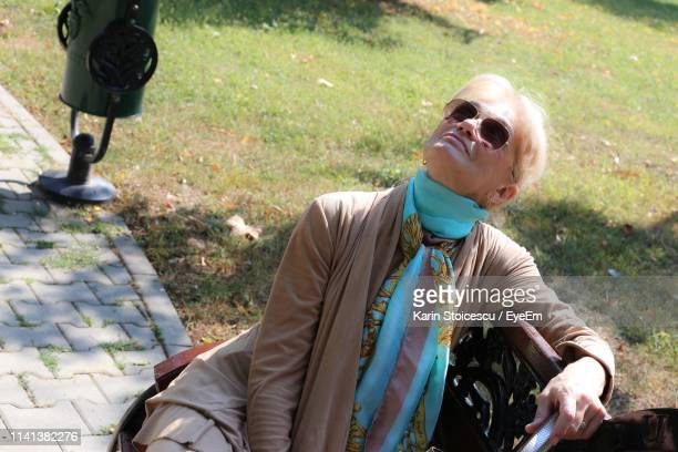 Woman Wearing Sunglasses While Sitting On Bench In Park
