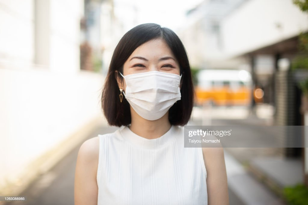 Woman wearing surgical mask and smiling : ストックフォト