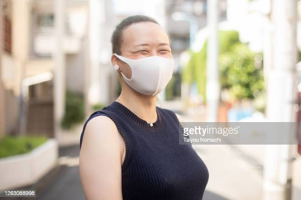 woman wearing surgical mask and smiling - ポジティブなボディイメージ ストックフォトと画像