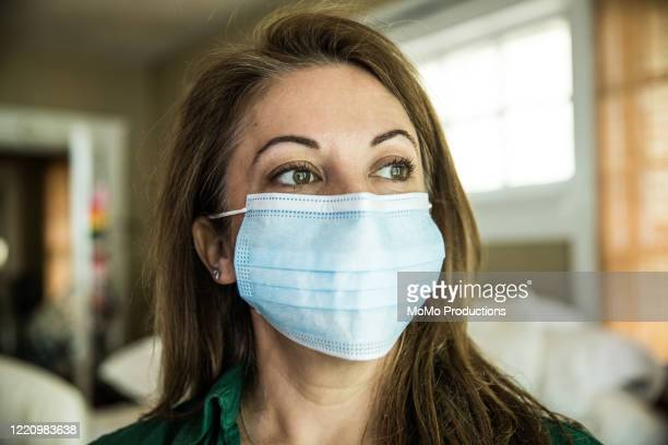 woman wearing surgical mask - healthcare stock pictures, royalty-free photos & images