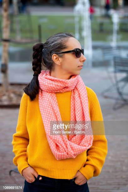woman wearing sweater and scarf looking away in city - florin seitan stock pictures, royalty-free photos & images