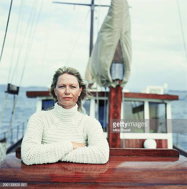 Woman wearing sweater, standing on bow of sailboat, portrait