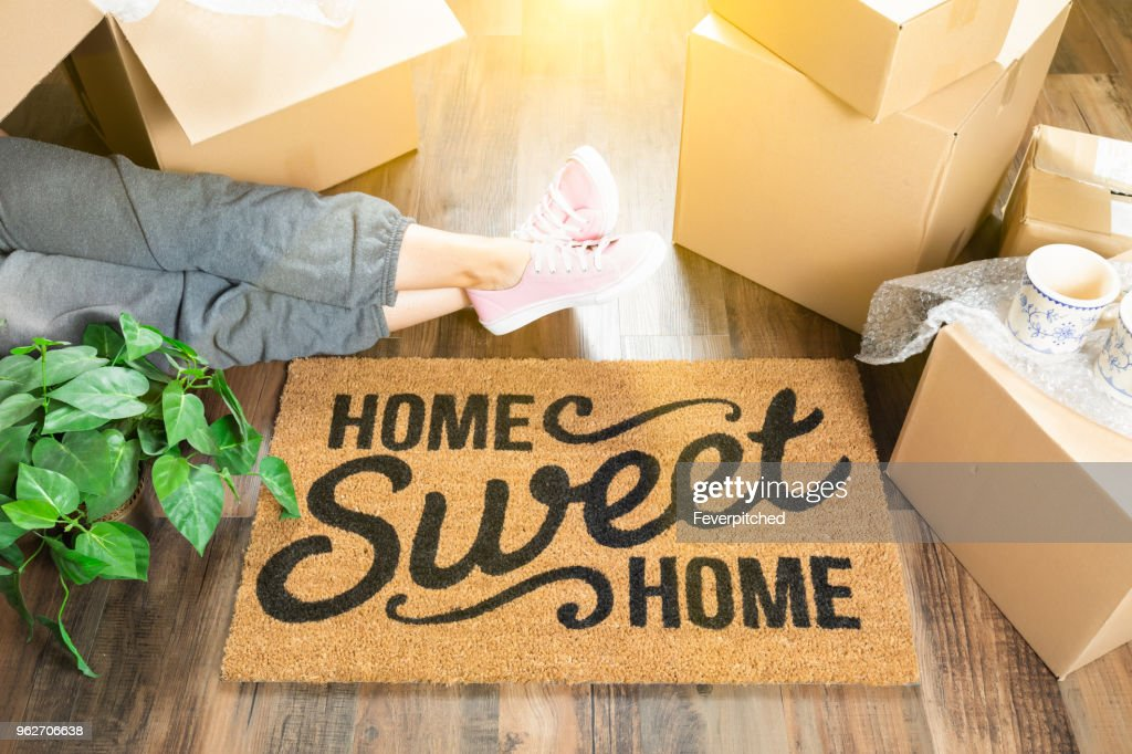 Woman Wearing Sweats Relaxing Near Home Sweet Home Welcome Mat, Moving Boxes and Plant. : Stock Photo