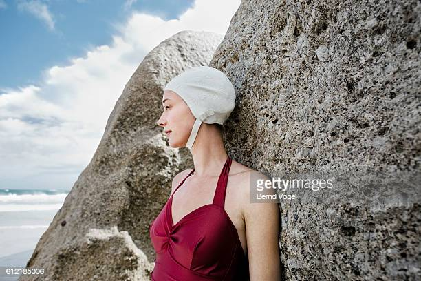 Woman Wearing Swim Cap Leaning Against Rock