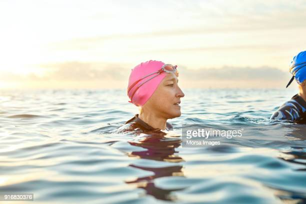 woman wearing swimming cap and goggles in sea - swimming goggles stock pictures, royalty-free photos & images
