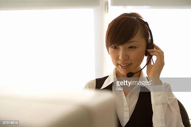 Woman wearing telephone headset, smiling
