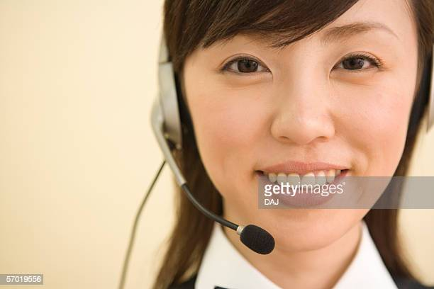 Woman wearing telephone headset, smiling, portrait