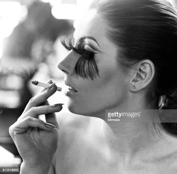 A woman wearing the longest eye lashes in the world smoking a cigarette 19th January 1968