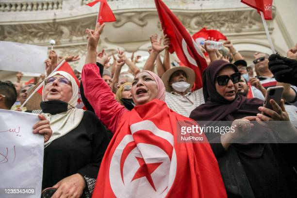 Woman wearing the Tunisian flag, makes victory sign as she chants slogans, during a demonstration held in the capital Tunis, Tunisia, on September 18...