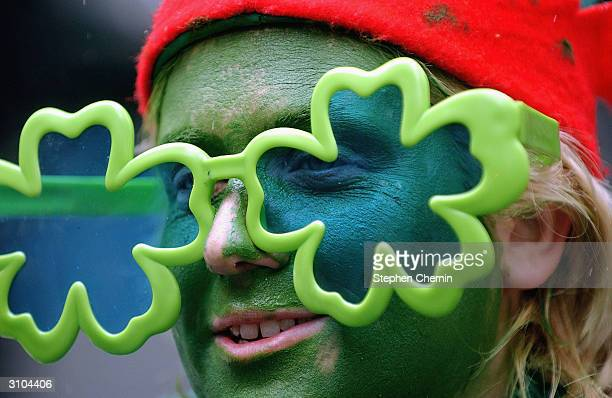 A woman wearing tinted shamrock glasses watches the 243rd Anuual St Patrick's Day Parade March 17 2004 in New York City