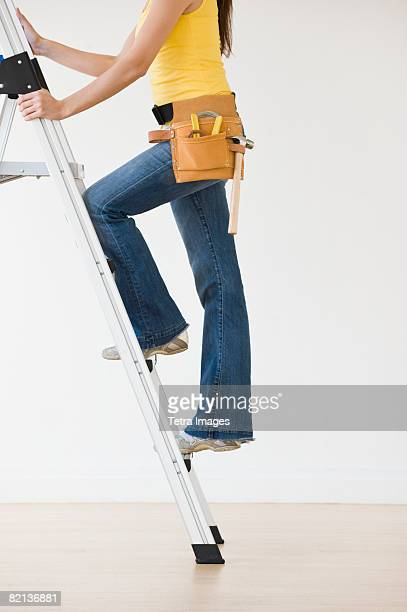 Woman wearing tool belt climbing ladder