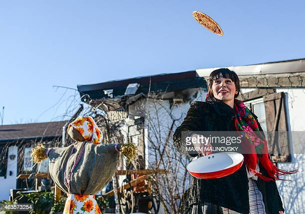 A woman wearing traditional Belarus' costume throws a pancake up in the air during the first day of Maslenitsa celebrations in Minsk on February 16...
