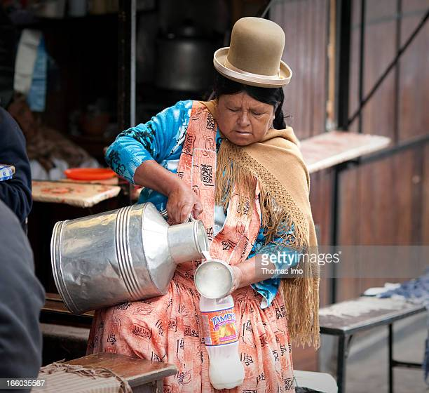 A woman wearing traditional Bolivian clothes is filling milk in a plastic bottle to sell it