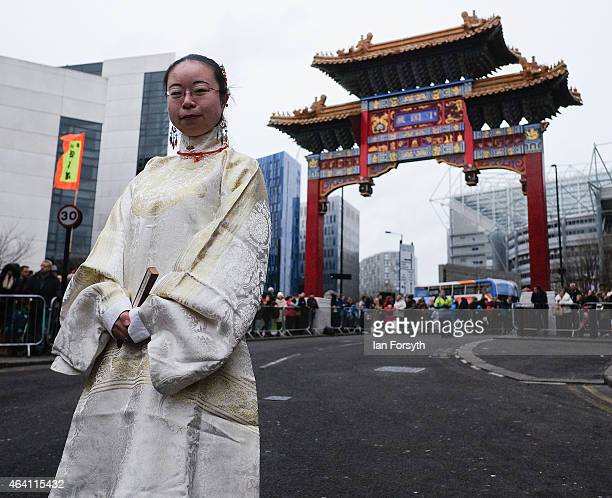 A woman wearing traditional Chinese clothing stands in front of the ceremonial archway as the Chinese community come together to welcome in the...