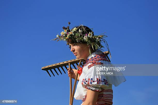 A woman wearing traditional clothes holds a rake while working on a meadow to mow in a traditional way in Mala Vrbka South Moravia 80 km southeast...