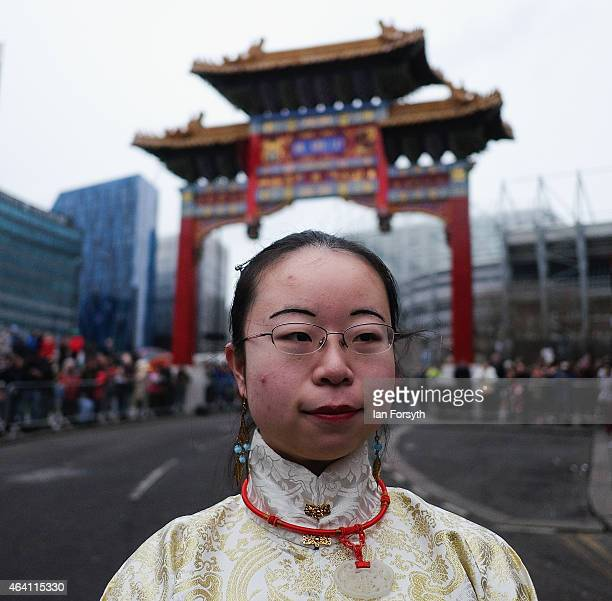 A woman wearing traditional clothing poses in front of the ceremonial archway as the Chinese community come together to welcome in the Chinese New...