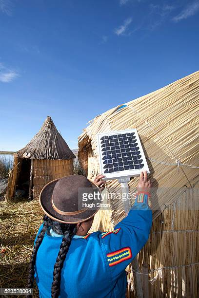 woman wearing traditional costume, using solar panel, on the uros islands of lake titicaca. puno, peru. - hugh sitton stock pictures, royalty-free photos & images