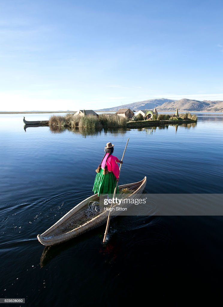 Woman wearing traditional costume, using traditionally made reed boat. The Uros Islands, Lake Titicaca. Puno. Peru. : Stock Photo