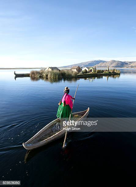 Woman wearing traditional costume, using traditionally made reed boat. The Uros Islands, Lake Titicaca. Puno. Peru.