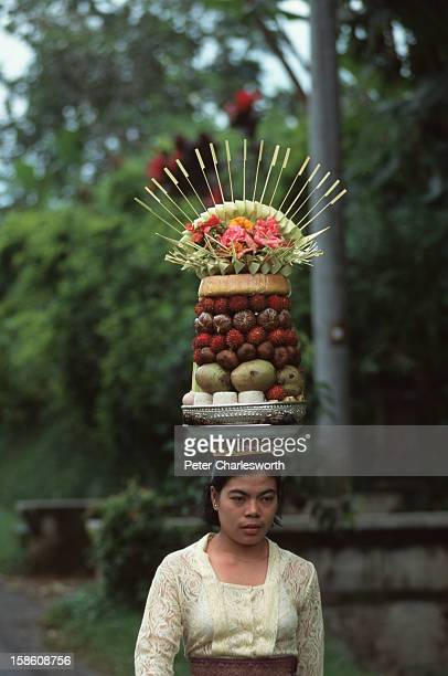 A woman wearing traditional dress carries on her head generous offerings to the gods a stacked plate of fruit and flowers as she arrives at a small...