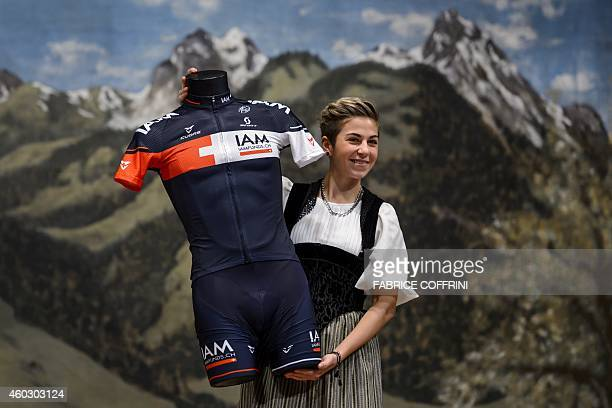 A woman wearing traditionnal dress shows the new outfit of IAM Cyling team during the presentation of the 2015 squad on December 11 2014 in Saanen...