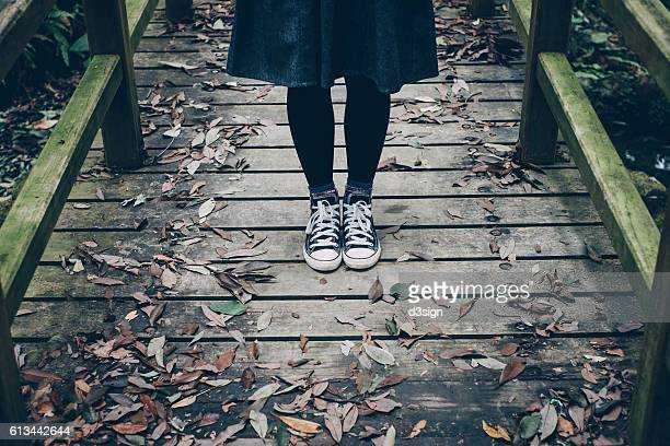 Woman wearing trainers standing on a wooden bridge with fallen Autumn leaves in forest