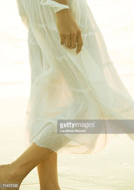 Woman wearing translucent skirt, low section