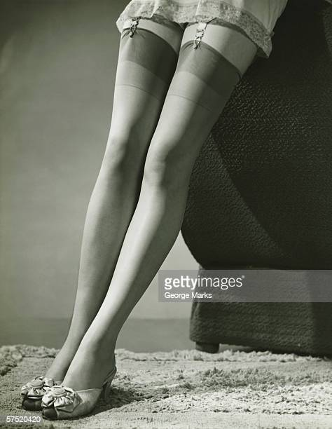 woman wearing underskirt and stockings, (b&w), low section - garter belt stock pictures, royalty-free photos & images