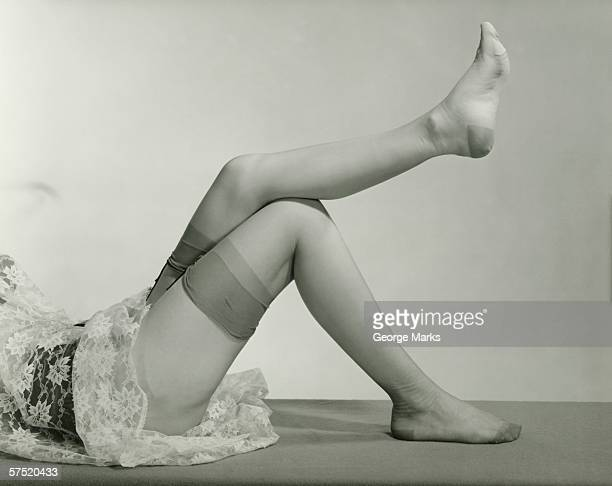 woman wearing underskirt and stockings lying on floor, (b&w), low section - vintage stockings stock photos and pictures