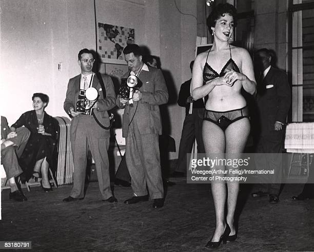 A woman wearing underwear and fishnet stockings and two photographers standing in a room waiting for the judging to commence New York 1950s Photo by...