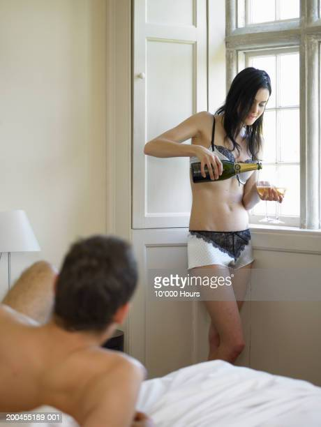 Woman wearing underwear, pouring champagne by man on bed