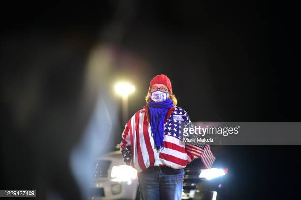 Woman wearing U.S. Flag clothing and a campaign-themed face mask attends a drive-in election-eve rally with Democratic vice presidential nominee Sen....