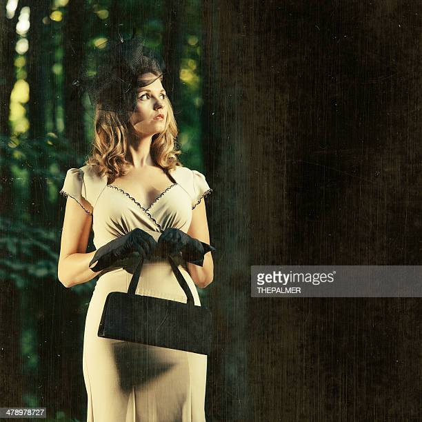 woman wearing vintage clothes in a dark forest