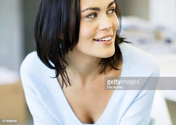 Woman wearing v-neck sweater, looking to the side and smiling, portrait