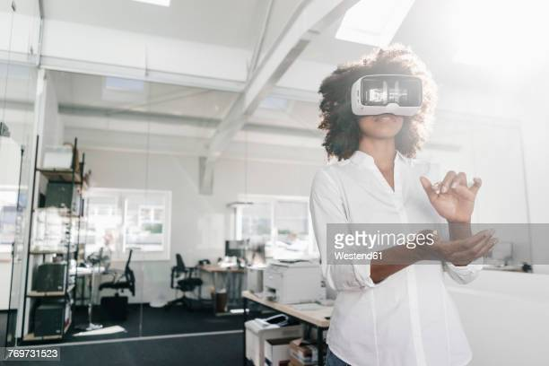 woman wearing vr glasses in office - simulatore di realtà virtuale foto e immagini stock